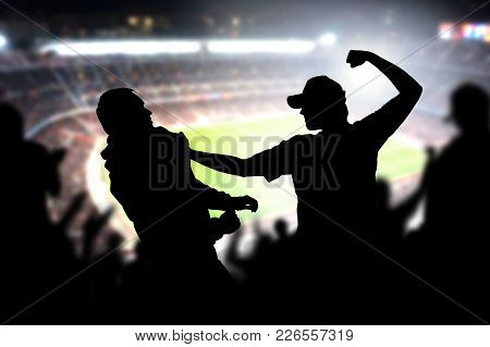 Fight In A Football Game Crowd. Angry Man Hitting Another Spectator In Soccer Match Audience. Violen