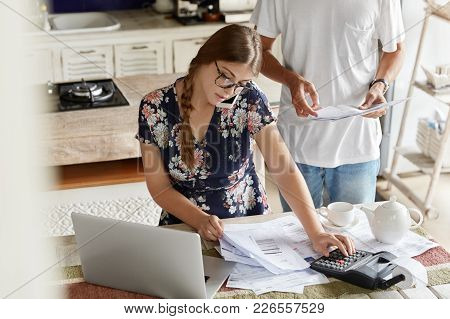 Photo Of Busy Female Makes Calculations, Pays Utility Bills, Works At Kitchen Table With Laptop Comp