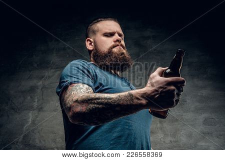 Fat Bearded Men With Tattoos On Arm Holds Beer Bottle.