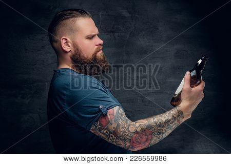 Bearded Male With Tattooed Arm Holds A Bottle Of Beer.