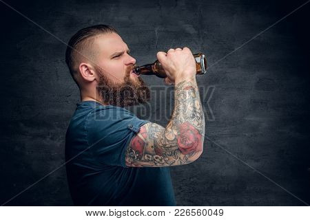 Brutal Bearded Male With Tattooed Arm Drinks A Beer From A Bottle.