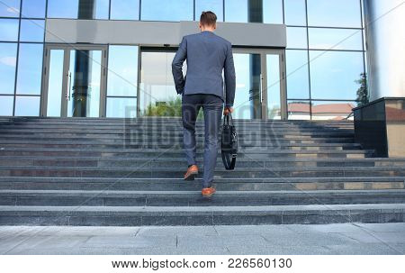 Business Executive With Briefcase Going Up The Stairs