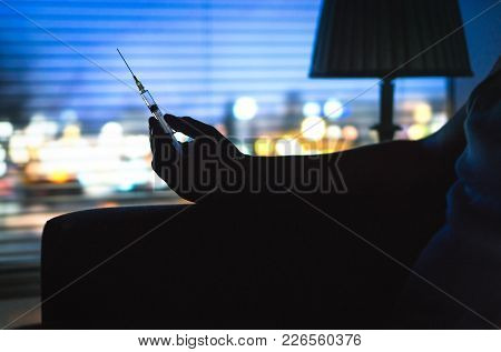 Drug Addict With Heroin Syringe Silhouette In Dark. Hand Holding Needle Late At Night. City Lights B