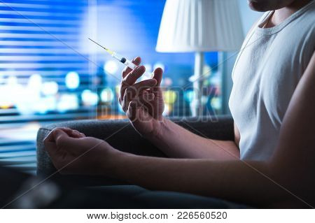 Drug Addict Holding Heroin Needle In Hand. Young Man With Hypodermic Syringe. Dramatic Addiction, Ov