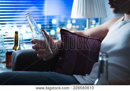 Drunk Man Sitting On Sofa And Holding A Bottle Of Alcohol. Alcoholic Drinking Home On Couch Late At