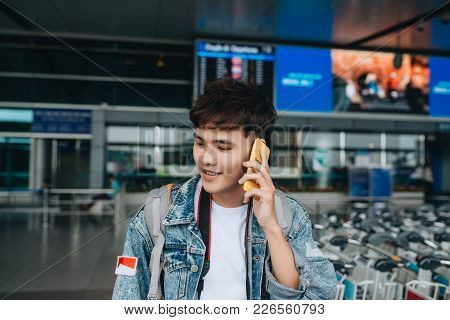 Portrait Of Smiling Man Texting While Waiting For Taxi In The Airport