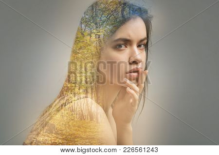 Sensible Glance. Young Calm Beautiful Woman Sitting Alone With Her Fingers Touching The Lips And Loo