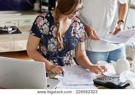 Cropped Shot Of Pretty Young Woman Uses Online Banking App On Laptop Computer, Calcualtes Something