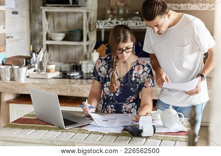 Pleasant Looking Housewife In Glasses, Makes Necessary Calculations, Writes Down Information With Pe