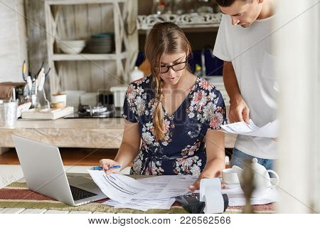 Serious Female Model Reviews Finances With Serious Expression, Thinks How To Cut Off Expenses, Works