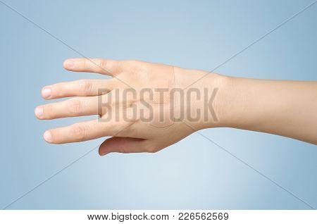 Female Hand With Adhesive Bandage On Blue Background