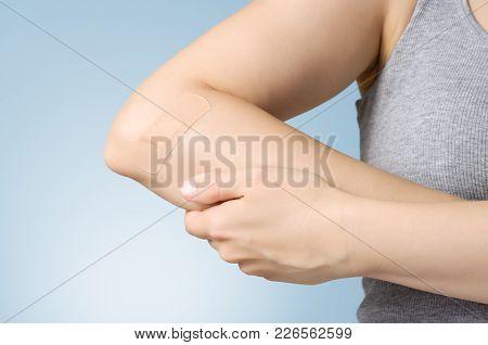 Female Arm With Adhesive Bandage On Blue Background