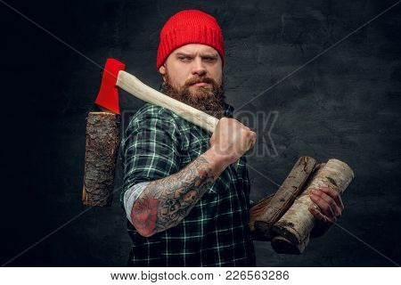 Portrait Of Bearded Lumberjack Dressed In A Green Shirt Holds The Red Axe.