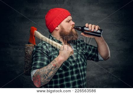 Brutal Bearded Lumberjack Wearing Green Plaid Shirt And Red Hat, Drinking Beer From A Bottle And Hol