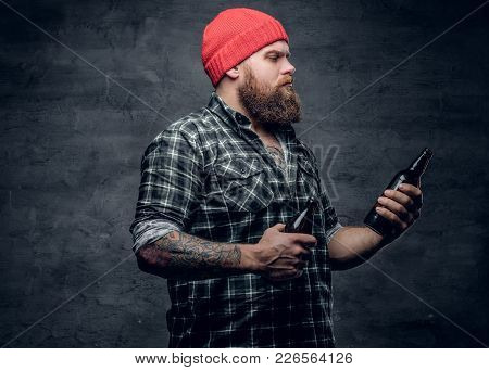 Portrait Of Bearded Male Dressed In A Plaid Shirt And Red Hat Holds A Beer Bottle In A Tattooed Arm.