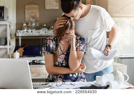 Indoor Shot Of Crying Woman And Husband Calms Her, Sits Together Against Kitchen Interior, Work With
