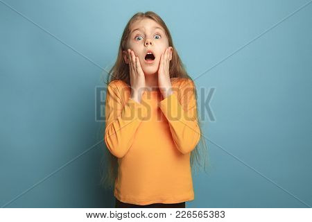The Surprise, Delight, Happiness, Joy, Victory, Success And Luck. The Surprised Teen Girl On A Blue