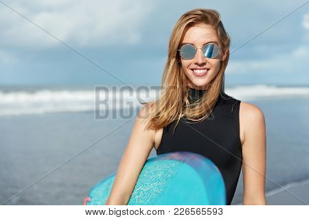 Young Attractive Sporty Female Wears Sunglasses And Swimsuit, Holds Surfboard, Smiles Happily, Going