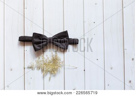 A Black Bow Tie Lies On A White Wooden Background