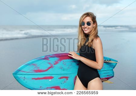 Outdoor Shot Of Beautiful Blonde Female In Swimsuit, Being In Good Mood, Ready To Conquer Most Dange