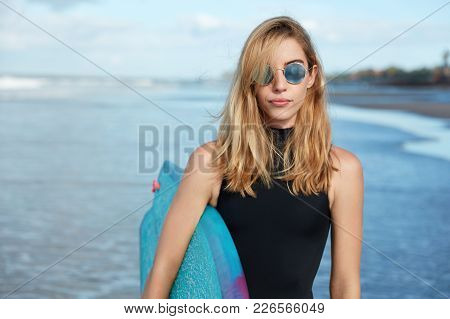 Good Looking Blonde Young Woman Wears Trendy Shades And Swimsuit, Holds Surfboard, Ready To Conquer