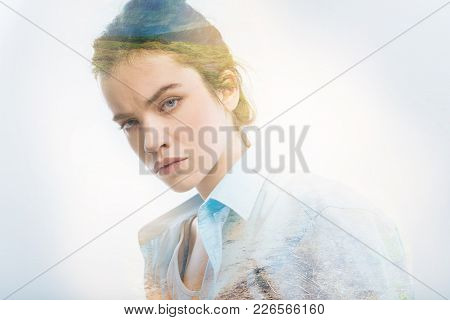 Serious Glance. Calm Young Clever Student Standing Against The Blue Background And Looking Serious W