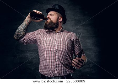 Portrait Of Bearded Male In A Plaid Shirt And A Cylinder Hat, Drinking Beer From A Bottle.