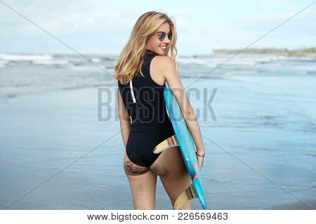 Back View Of Young Pretty Woman With Slender Body, Wears Black Swimsuit, Holds Surfboard, Ready To R