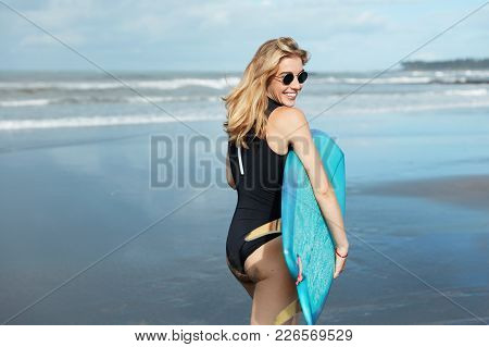 Outdoor View Of Blonde Female Surfer Holds Surfboard, Dressed In Swimwear, Wears Sunglasses, Stands