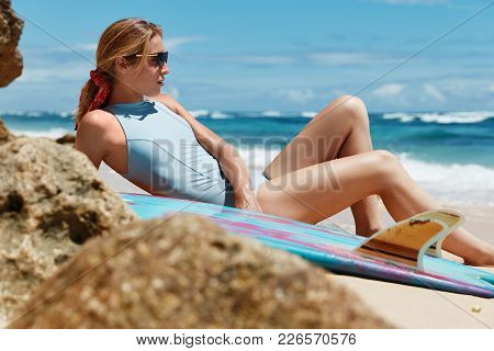 Outdoor Shot Of Dreamy Sexy Female Surfer In Blue Swimsuit Lies On Sandy Beach With Surf Board, Admi