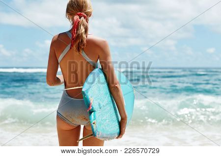 Slim Sporty Female Stands Back Outdoor, Has Fit Butt, Dressed In Swimwear, Carries Kite Board Under