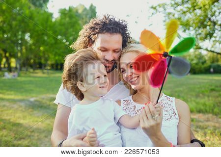 Happy Family Playing In The Park. Mother, Father And Son Play Together In Nature In The Summer, In T