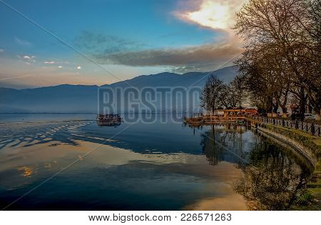 Sunset Over Ioannina City And Lake Pamvotis. Seafront Street For Cars,pedestrians And Bicycles .epir