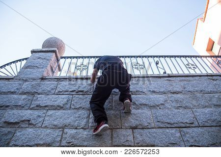 Young Man Hanging On Wall And Trying To Climb Up While Doing Parkour.
