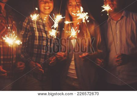 Young Happpy People With Sparklers Having Fun On Outdoor Party