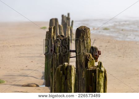 Wooden Post In The Morning Dust At Sandsend Beach, Near Whitby, North Yorkshire, Uk