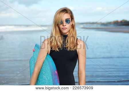 Good Looking Blonde Young Woman Wears Trendy Sunglasses And Swimsuit, Carries Blue Surfboard, Walks