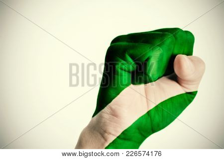 closeup of the fist of a young caucasian man patterned with the flag of Andalusia, Spain, against an off-white background, with a slight vignette added