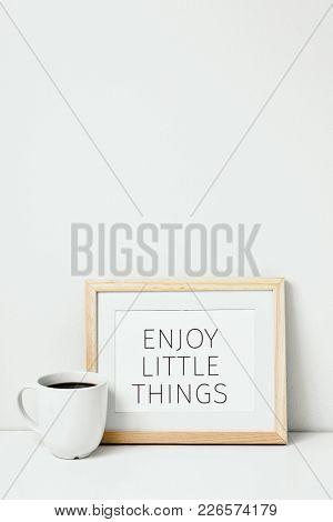 a wooden-framed picture with the text enjoy little things written in it and a cup of coffee, on a whit table against a white background with some blank space on top