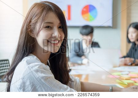 Portrait Of Young Asian Woman In Office With Coworkers Talking In Background. Female Creative Profes