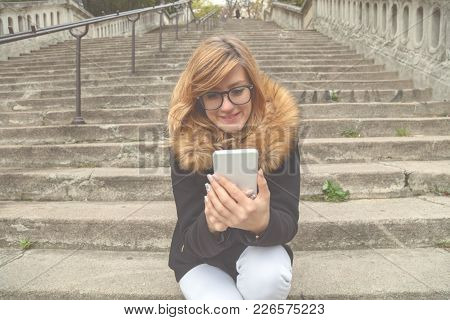 Cute Girl Using Cellphone While Sitting On A Big Staircase.