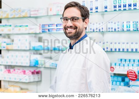 Apothecary in pharmacy standing at shelf with drugs smiling