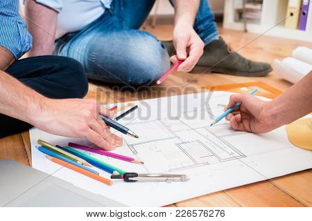 Team of architects and civil engineers sitting on floor with construction plans spreaded