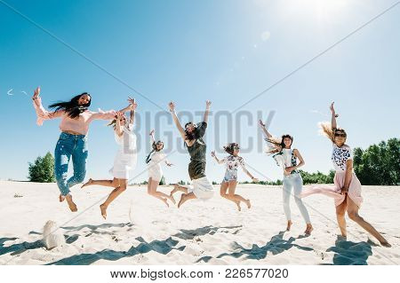 Beautiful Stylish Happy Sexy Slim Young Girls Jump On Sand Beach. Party In Style Boho. Maiden Evenin