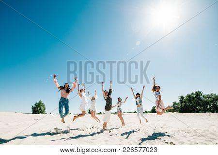 Beautiful Stylish Happy Sexy Slim Young Girls Jump On Sand Beach. Hands Decorated Buttonhole, Butoni