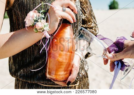 Girl Holds Champagne And Glass. Glass, Hand Decorated With Ribbons Flowers. Party In Style Boho. Mai