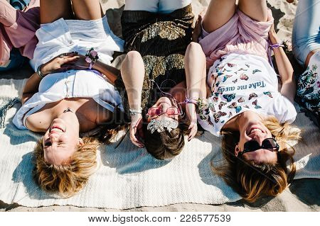 Beautiful Happy Stylish Sexy Young Girls Lying On Sand Beach On Blanket. Show Sincere Smiles. Party
