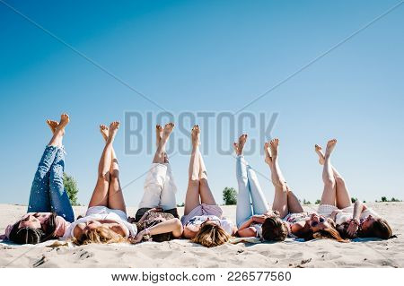 Beautiful Happy Slim Stylish Sexy Young Girls Lying Down On The Sand Beach And Putting Their Feet Up