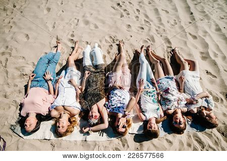 Beautiful Happy Slim Stylish Sexy Young Girls Lying Down On Sand Beach Show Long Legs. Party In Styl