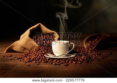 steaming cup of coffee with jute bag, scoop and coffee beans
